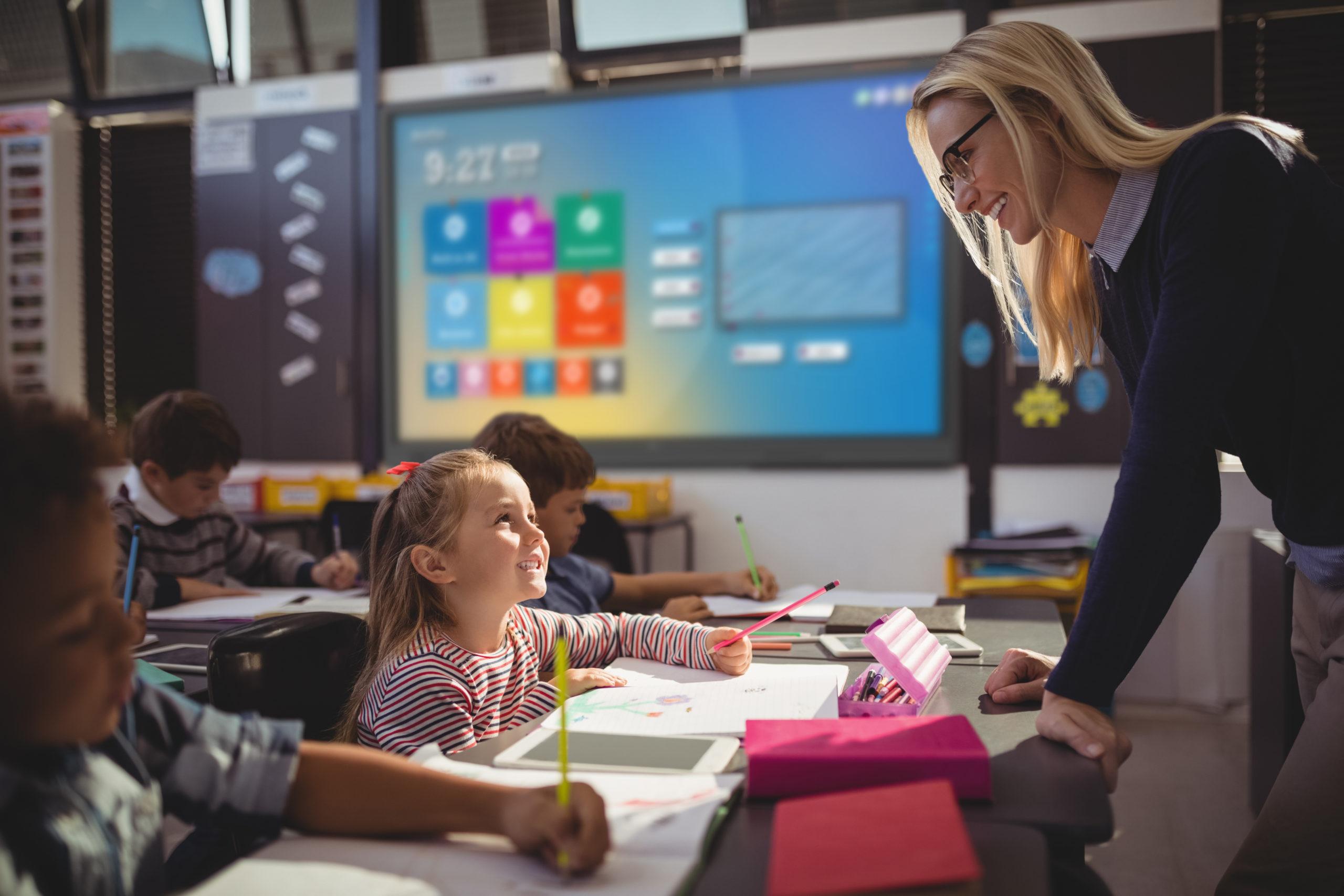 Teacher interacting with schoolgirl in classroom